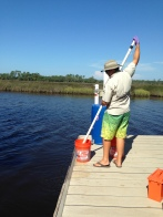 SWMP Technician, Silas Tanner, collecting water for nutrient analyses