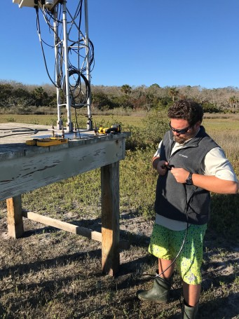 Silas, SWMP Technician, repairing the grounding wire at the weather station